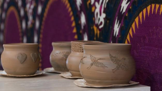 Свеже сделанные глиняные горшки на декоративном фоне. детские поделки