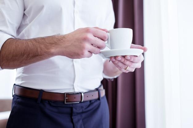 Свежеприготовленный кофе. крупный план чашки с кофе, находящейся в руках красивого умного успешного предпринимателя