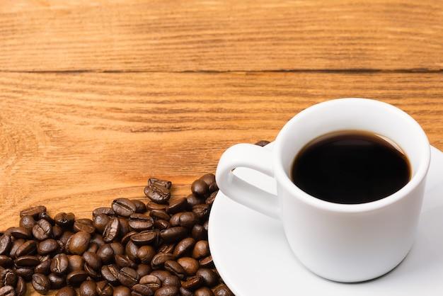 木製のテーブルでコーヒー豆に囲まれた白いカップで淹れたてのコーヒー。焼きたてのコーヒー。
