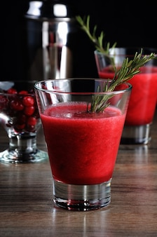 Свежеприготовленный клюквенный сок с веточкой розмарина