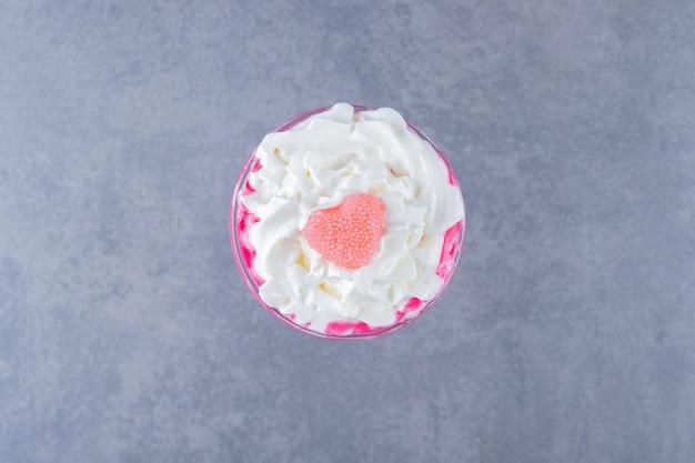 Frullato di latte rosa cremoso appena fatto su sfondo grigio.