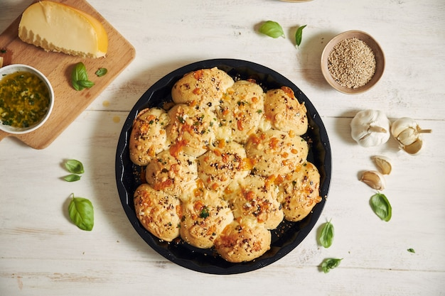 Свежеприготовленный вкусный сырный хлеб для пиццы с пузырьками с ингредиентами и сыром на белом столе