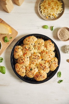 Freshly-made delicious cheese bubble pizza bread with ingredients and cheese on a white table