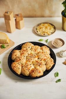 Delizioso pane per pizza con bolle di formaggio appena fatto con ingredienti e formaggio su un tavolo bianco