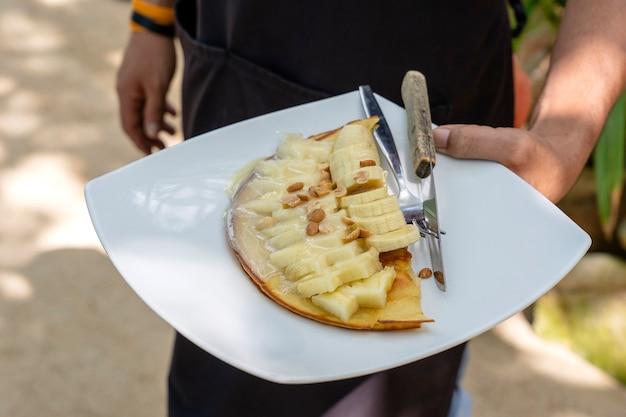 Свежеприготовленные вкусные блины с бананами, орехами на белой тарелке. мужчина держит тарелку с блинами. руки держат тарелку. вкусный домашний завтрак. идеи здорового завтрака.
