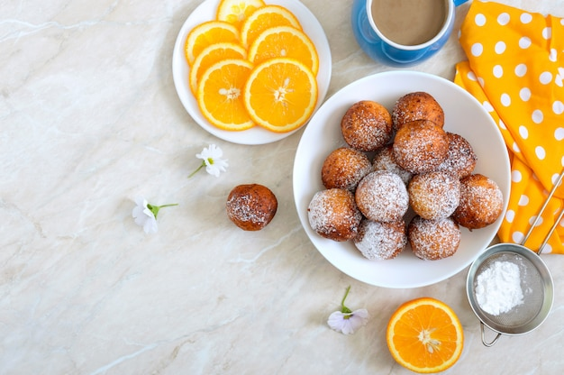 Freshly made donuts with powdered sugar in a white bowl, copy space. curd balls fries. dessert from the cottage cheese