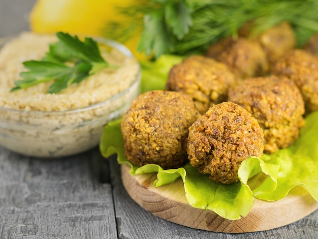 Freshly made falafel on a cutting board with sauce tahina and parsley and lemon