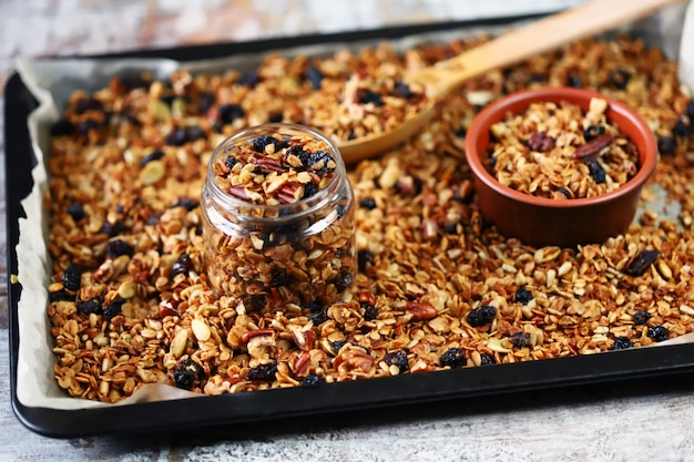 Freshly made homemade granola on a baking sheet with a wooden spoon and jars