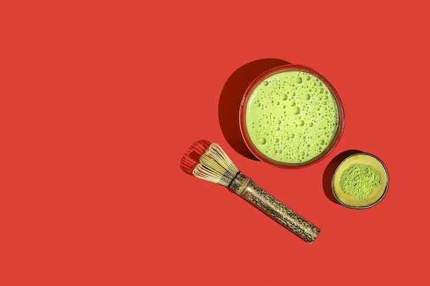 Свежеприготовленный чай матча с ингредиентами на красном фоне. вид сверху.