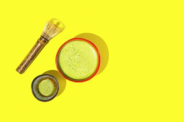 Свежеприготовленный чай матча с ингредиентами на желтом фоне