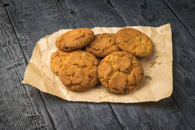 Freshly made oatmeal cookies on paper on a black wooden table