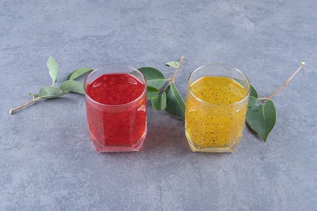 회색 배경에 갓 만든 오렌지와 석류 주스.