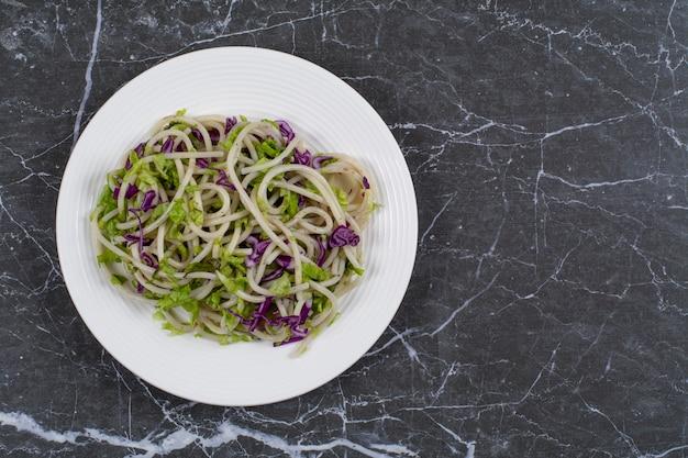 Свежеприготовленные спагетти с овощным соусом на белой тарелке.