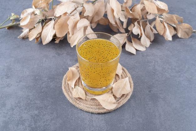 Succo di mandarino appena fatto su sfondo grigio.