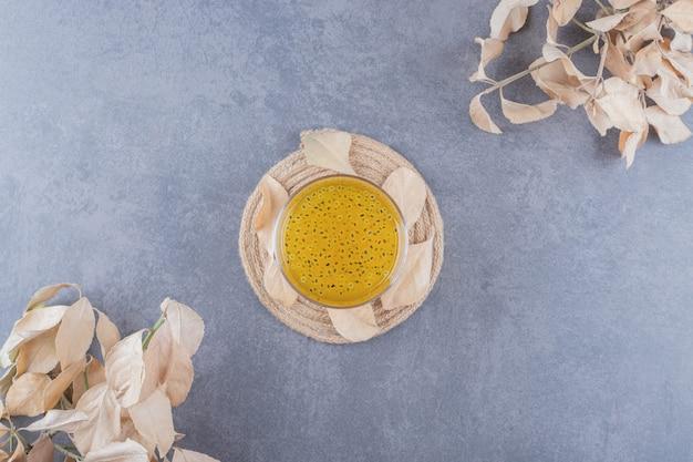 Succo di mandarino appena fatto sulla tavola di legno su sfondo grigio.