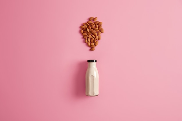 Freshly maked almond milk in glass bottle to substitute dairy product for vegetarians. rosy background, top view. healthy vegetarian natural drink. diet, health care, proper nutrition concept