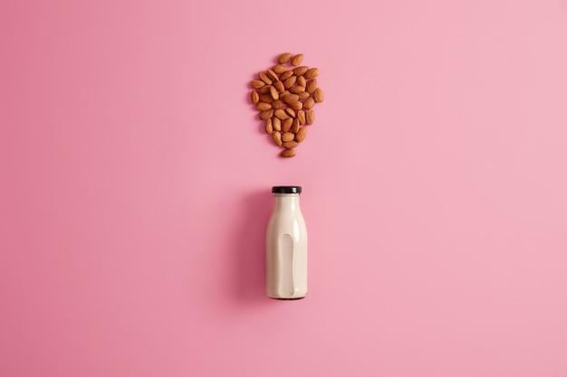 채식주의자를 위해 유제품을 대체하기 위해 유리 병에 갓 만든 아몬드 우유. 장미 빛 배경, 평면도. 건강한 채식 천연 음료. 다이어트, 건강 관리, 적절한 영양 개념