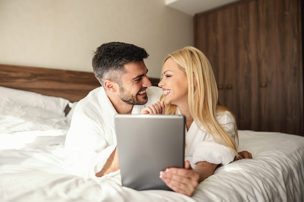 Freshly married couple kissing and tenderness in a comfortable bed with white sheets