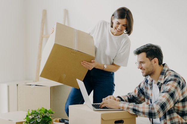 Freshly married family couple pose in their new apartment, unpack boxes with belongings