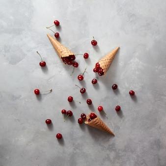 Свежие натуральные органические вишневые фрукты с вафельными рожками на сером фоне, копией пространства. вид сверху. летняя концепция домашнего печенья.