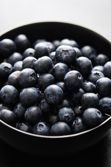 Freshly picked blueberries in black bowl on the table.