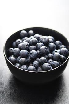 Freshly picked blueberries in black bowl.