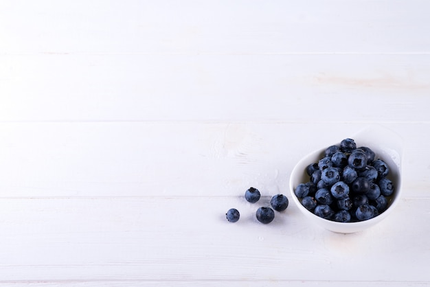 Freshly picked blueberries in bowl on white wood