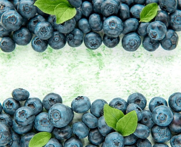 Freshly picked blueberries on a green wooden background. concept for healthy eating