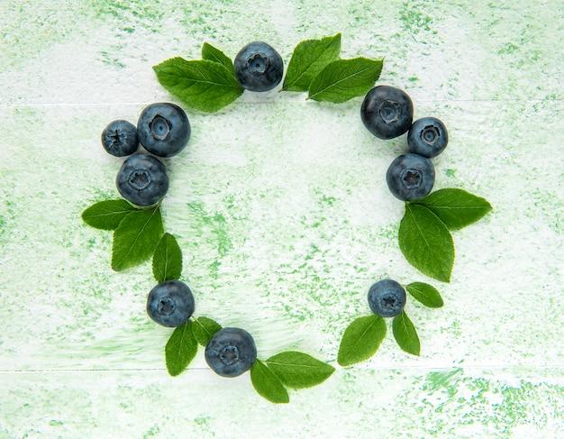 Свежесобранная черника на зеленом деревянном фоне. концепция здорового питания