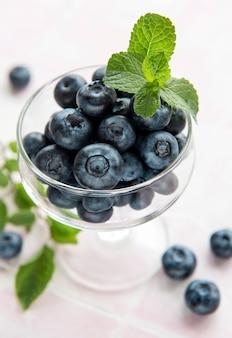 분홍색 타일 배경에 갓 고른 블루베리입니다. 건강한 식생활을 위한 개념