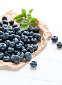 흰색 타일 배경에 갓 고른 블루베리입니다. 건강한 식생활을 위한 개념