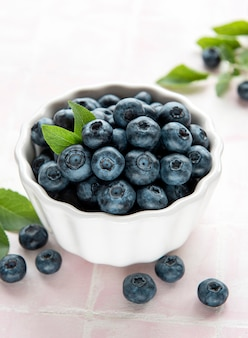 Freshly picked blueberries on a pink tile background. concept for healthy eating