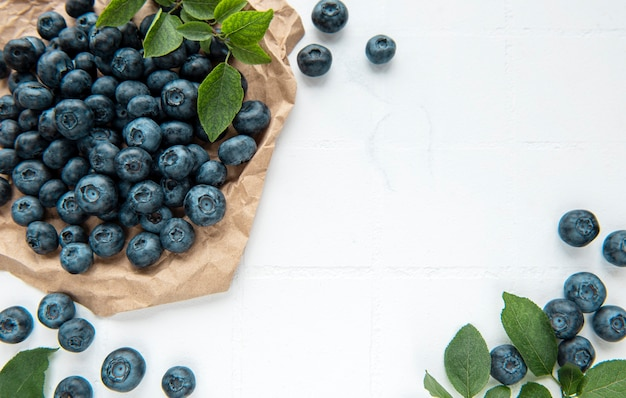 Freshly picked blueberries on a white tile background. concept for healthy eating