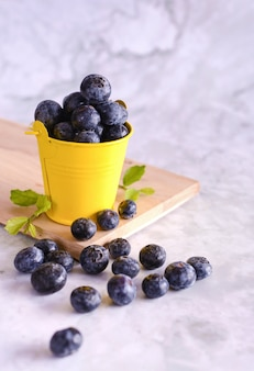 Freshly picked blueberries in yellow can