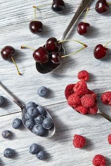 회색 나무 배경에 갓 고른 과일입니다. 다채로운 유기농 딸기 패턴입니다. 건강한 유기농 식사의 개념입니다. 플랫 레이