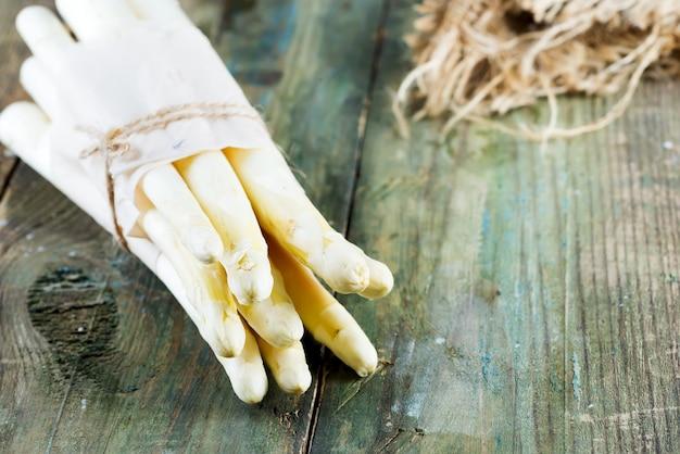 木製の背景にホワイトアスパラガス野菜の採れたての自然有機束。