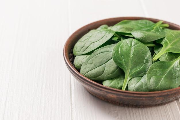 흰색 테이블에 갓 고른 시금치 잎. 건강을 위한 음식. 채식주의 자 음식. 정상에서 본 모습.