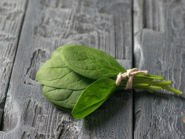 갓 고른 시금치 잎은 나무 테이블에 밧줄로 묶여 있습니다. 건강을 위한 음식. 채식주의 자 음식.