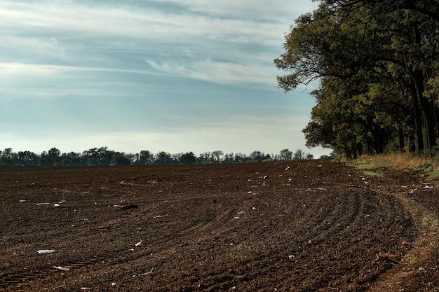 地面にプラスチック廃棄物がある耕されたばかりの畑