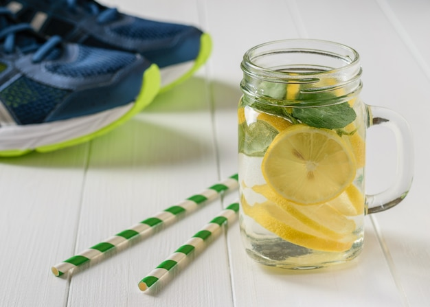 A freshly prepared drink made of lemon and mint on the background of sneakers wooden floor