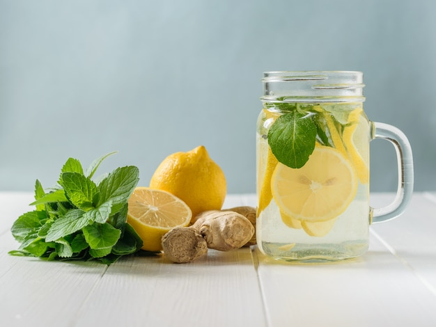 A freshly prepared drink made of lemon and mint on a wooden floor