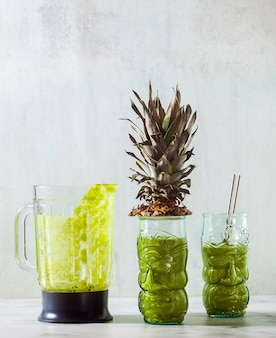 Freshly prepared green pineapple smoothie in glasses with faces. healthy morning breakfast concept.