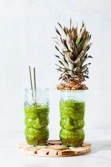 Свежеприготовленный зеленый ананасовый смузи в очках с лицами. концепция здорового утреннего завтрака.