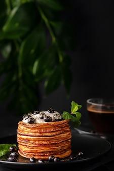 サワー クリームと新鮮な果実を添えた作りたての自家製パンケーキ、香り高いコーヒー カップでフード ゴールドで飾られています。