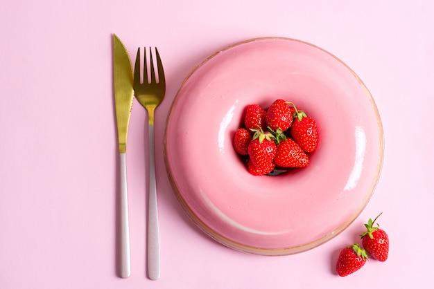 黄金のフォークとピンクの背景にナイフで作りたての自家製ストロベリーフルーツデザート。