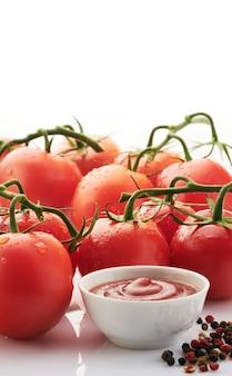 白いコピースペースに完熟した赤いトマトを添えた作りたてのケチャップ。