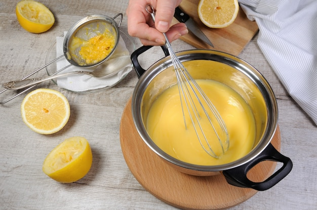 갓 준비한 레몬 커드 - 거품기로 휘핑한 스튜 냄비에 과일 주스에 커스터드