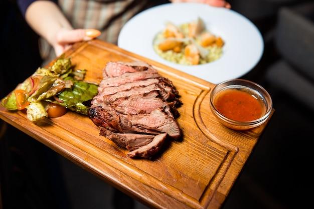 Свежеприготовленный мясной стейк, нарезанный кусочками на деревянной доске, подается с соусом и зеленым салатом