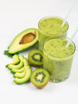 A freshly prepared smoothie of avocado, banana, orange, lemon and kiwi on a white table. diet vegetarian food. raw foods.