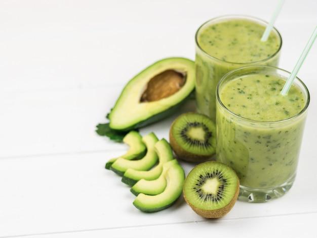 A freshly prepared smoothie of avocado, parsley, lemon and kiwi on a white table diet vegetarian food